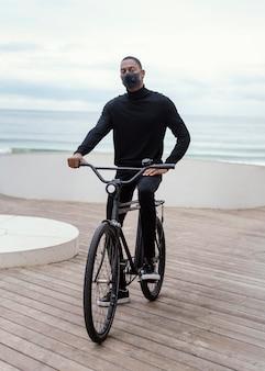 Uomo che indossa la maschera in sella alla sua bici in città