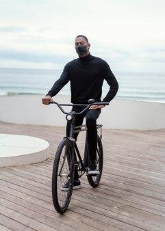街で自転車に乗ってマスクをしている男