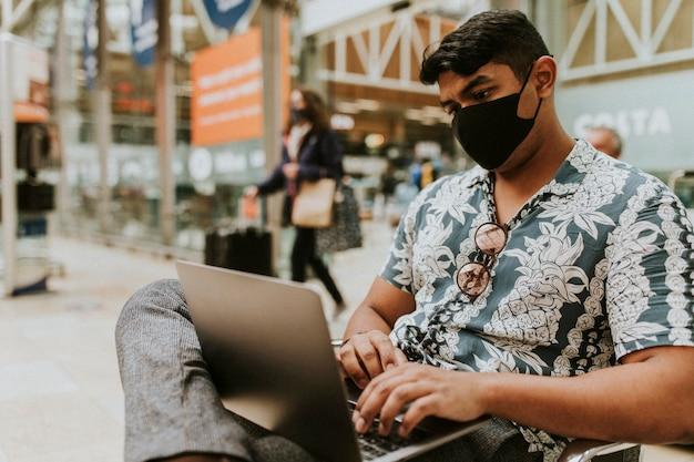 Человек в маске с ноутбуком на вокзале в новой норме