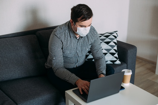 Man wearing mask working with laptop from home office