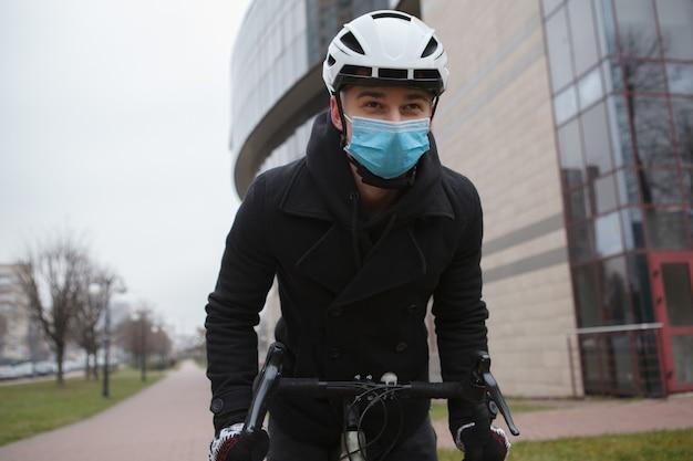 自転車に乗っている間、医療用フェイスマスクと保護サイクリングヘルメットを着用している男性
