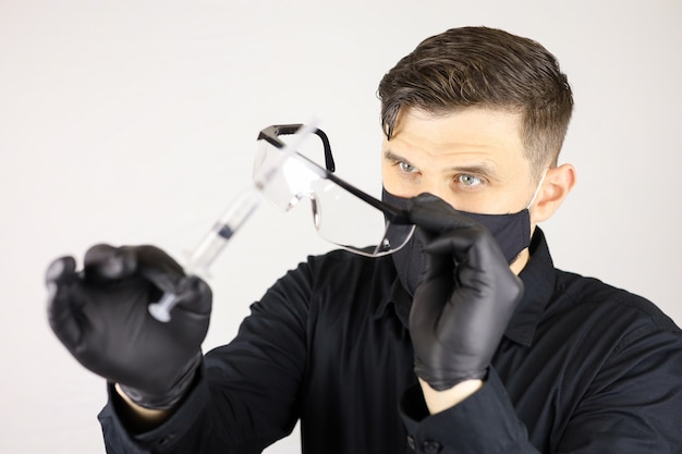 A man wearing medical gloves glasses and a protective mask with a syringe in his hand on a white background