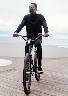 医療用マスクを着用して自転車に乗る男