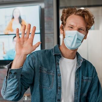 Мужчина в медицинской маске и машет рукой