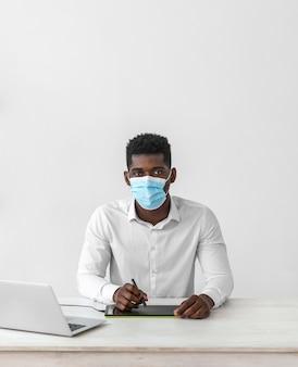 職場の正面図で医療マスクを着用している男性