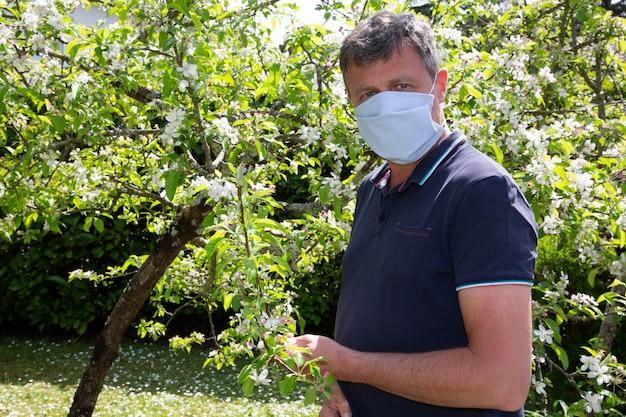 リンゴの木の近くの家の庭の検疫でコロナウイルスに対して自家製の医療マスクを着た男