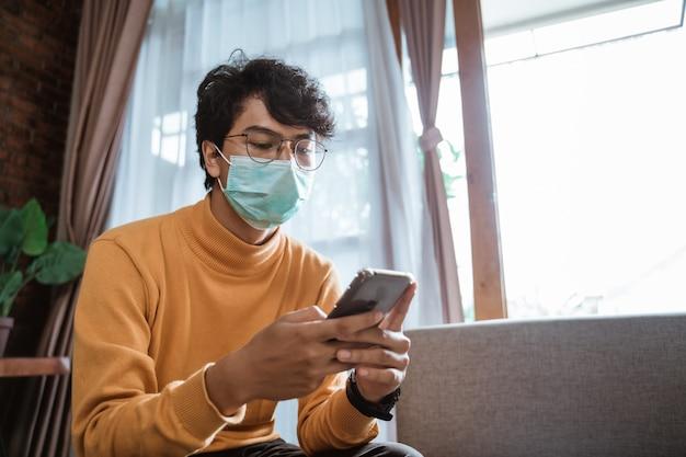 Человек, носящий медицинские маски с помощью мобильного телефона во время блокировки эпидемии вируса