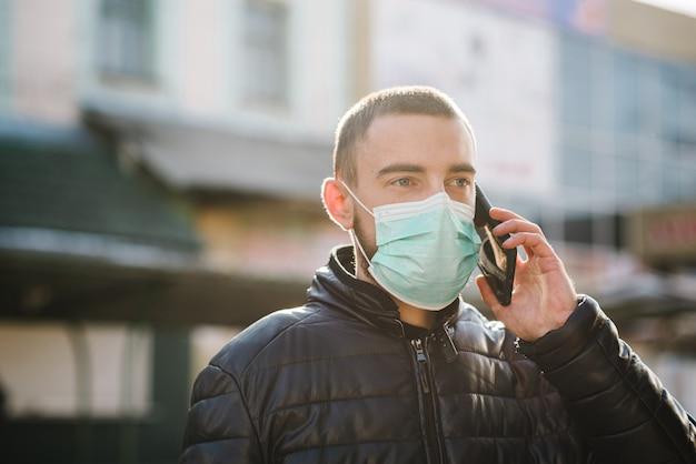 通りを歩いて医療用防護マスクを着用し、携帯電話で話している人。 covid-19、インフルエンザを防ぎます。ウイルス、パンデミック、パニックの概念。コロナウイルス。