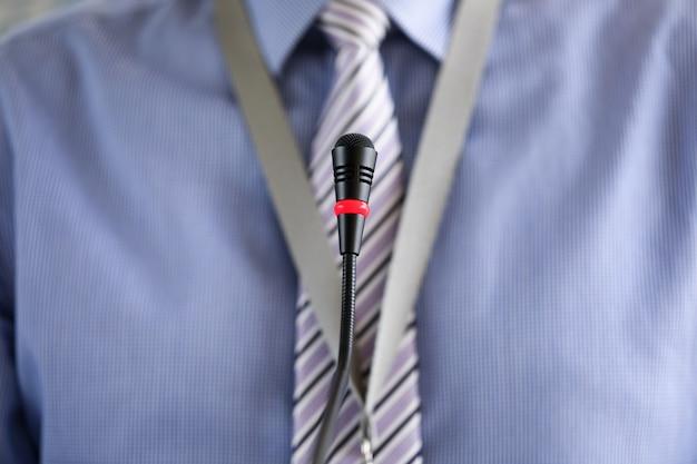 会議マイクに立っているネクタイを着た男
