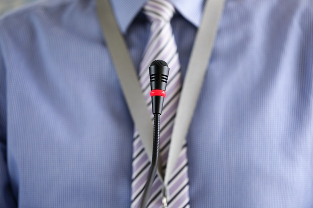 Man wearing necktie standing at conference microphone