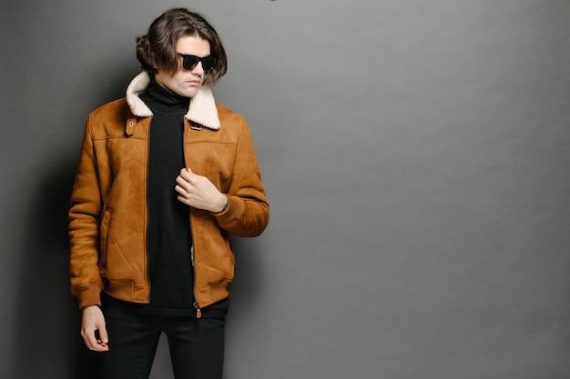 회색 질감 위에 주황색 코트를 입고 남자