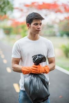 A man wearing orange gloves collecting garbage in a black bag.