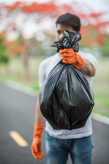A man wearing orange gloves collecting garbage in a black bag.