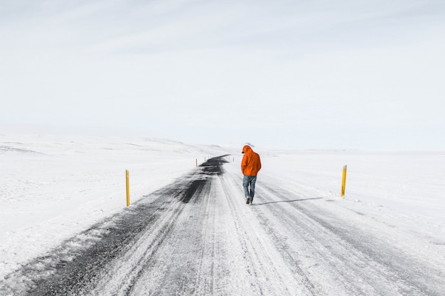 Man wearing orange jacket walking along a snowy highway road