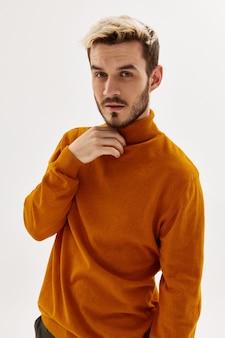 Man wearing orange sweater holding collar and posing