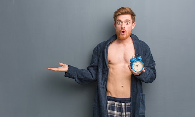 Man wearing pajama holding a clock