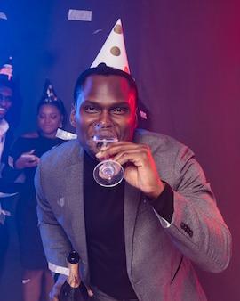 パーティーハットをかぶってシャンパンを飲む男