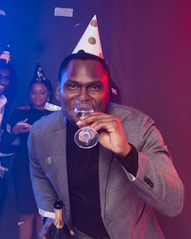 Uomo che indossa cappello da festa e beve champagne