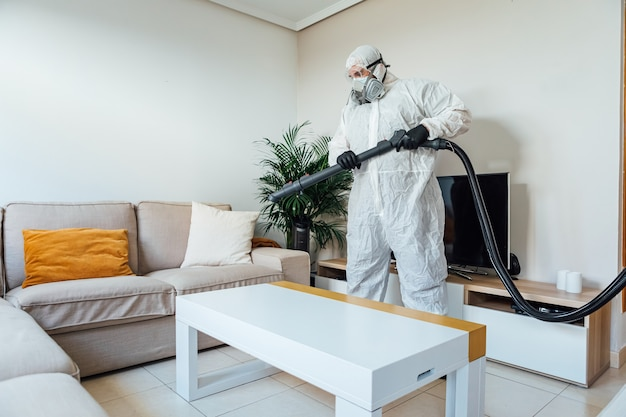 Мужчина в сиз дезинфицирует жилую комнату дома с помощью дезинфицирующего устройства covid-19. концепция здравоохранения пандемии
