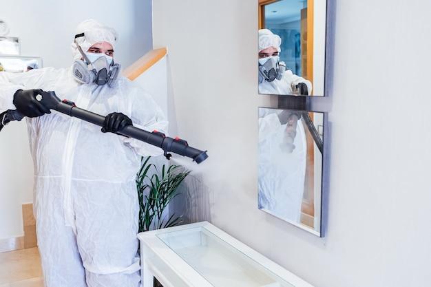 Мужчина в сиз внутри дома дезинфицирует стеклянный стол от covid-19. концепция здравоохранения пандемии