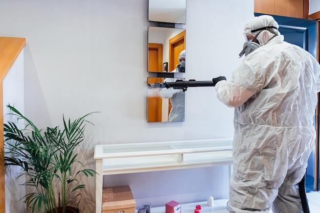 Мужчина в сиз внутри дома дезинфицирует зеркало от covid-19. концепция здравоохранения пандемии