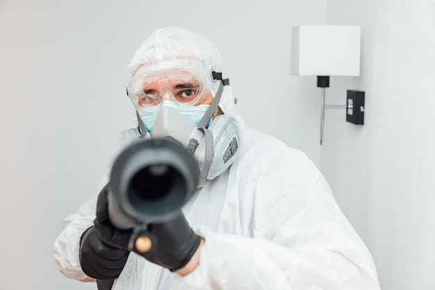 Мужчина в сиз направляет дезинфицирующий аппарат covid-19 в камеру. концепция здравоохранения пандемии