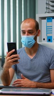 Человек в защитной маске с помощью веб-камеры смартфона, имеющей виртуальную встречу. фрилансер, работающий в новом обычном офисе, болтает, разговаривает на виртуальной конференции, используя интернет-технологии