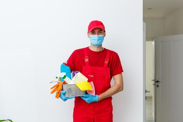 保護マスクを着用し、白い背景の上のクリーニング用品とバスケットを保持している男