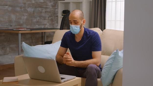 코로나바이러스 잠금 기간 동안 노트북으로 전화 회의를 하는 동안 보호 마스크를 쓴 남자.