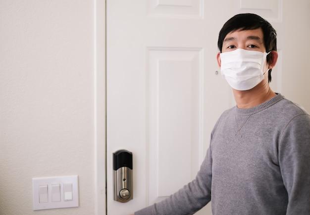 문 옆에 보호 마스크를 착용하는 남자