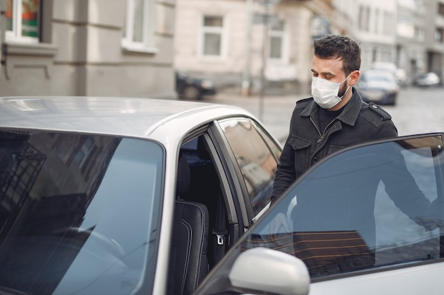 Man wearing a protective mask getting into in a car