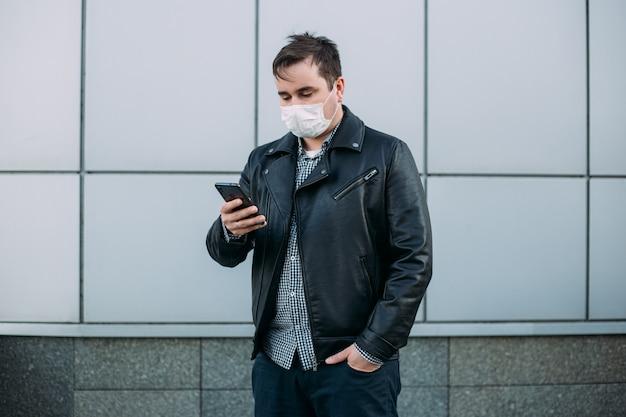 Man wearing protective mask at street using smartphone