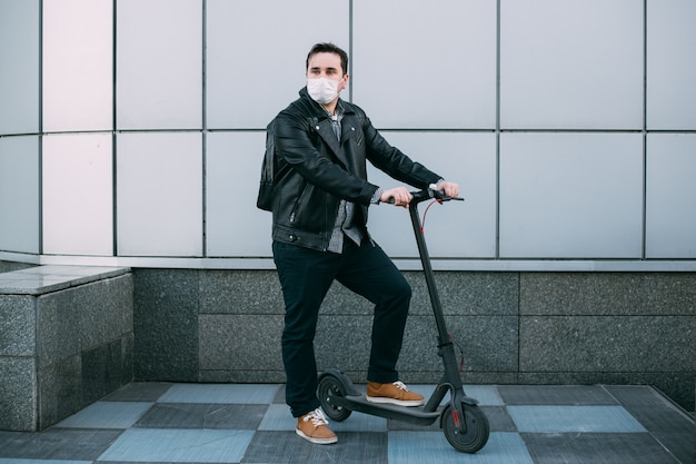 Man wearing protective mask using electric scooter