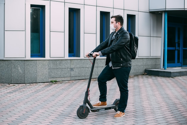 Man wearing protective mask using scooter