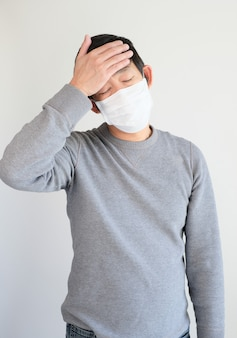 Man wearing protective mask with headache
