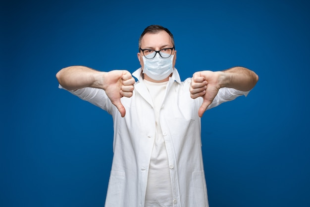 Man wearing protective mask with thumbs dow