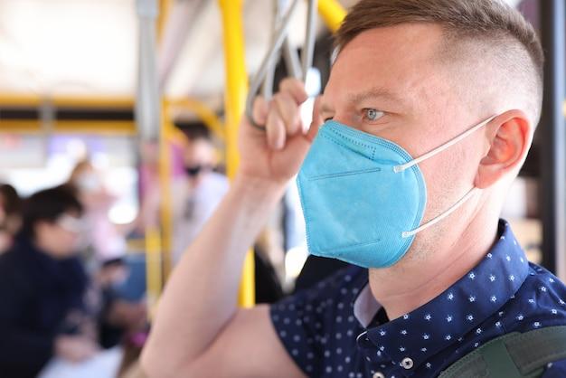 Человек в защитной медицинской маске едет на автобусе и держится за поручень