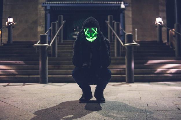 プルオーバーパーカーと緑のledマスクを身に着けている男