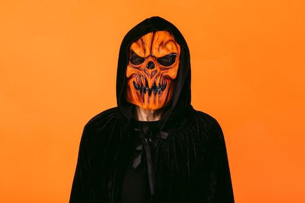 オレンジ色の背景に、カボチャのラテックスマスクとフード付きのベルベットのケープを身に着けている男。ハロウィーンと死んだコンセプトの日々。