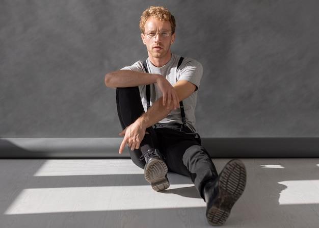 Uomo che indossa gli occhiali da lettura seduto sul pavimento