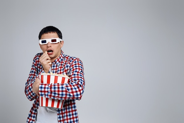 Man wearing red-blue 3d glasses and eating popcorn from bucket while watching a horror movie isolated on gray