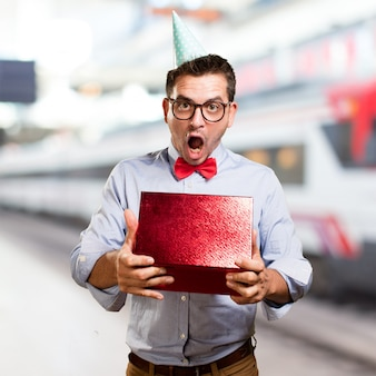 Man wearing a red bow tie and party hat. holding gift. looking s