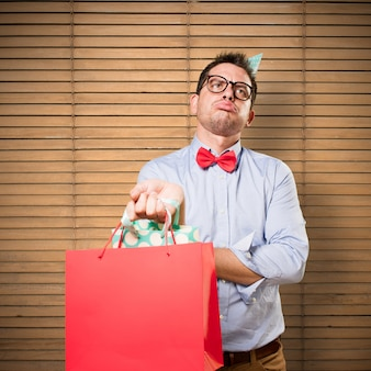 Man wearing a red bow tie and party hat. holding gift. looking t