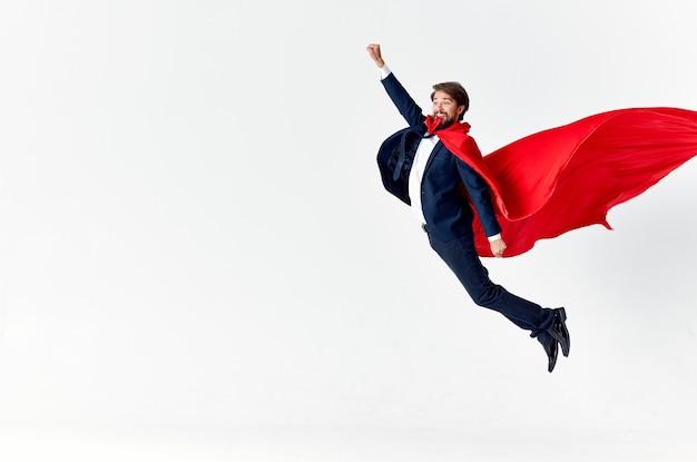 赤いマントを着た男スーパーマンジャンプ