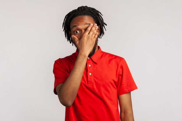 Man wearing red casual style tshirt spying through hole in fingers closing eyes with palm peeking