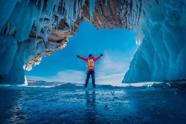 男は赤い服を着て、氷の洞窟で凍った水の上に立って腕を上げる