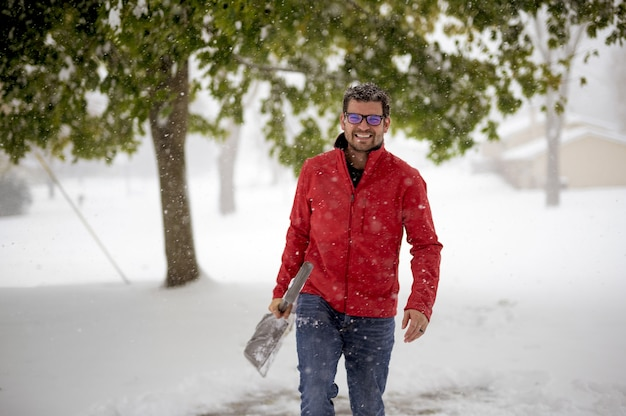 Man wearing a red jacket and walking in a snowy field while holding the snow shovel