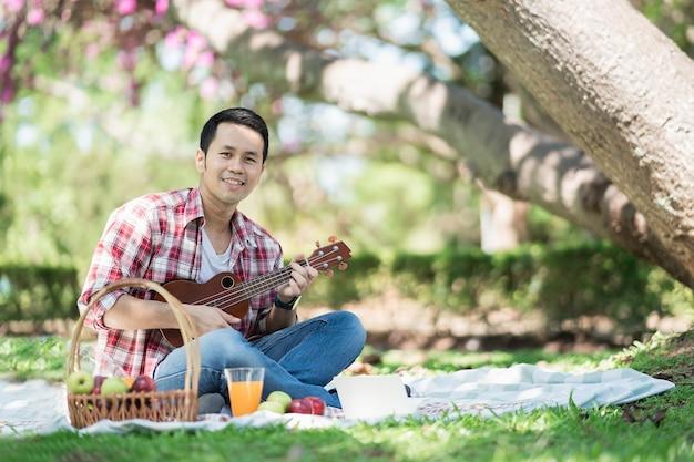 Man wearing red shirt playing ukulele and reading book