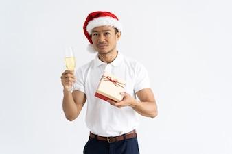 ギフトボックスとゴブレットを持って、サンタの帽子を身に着けている男
