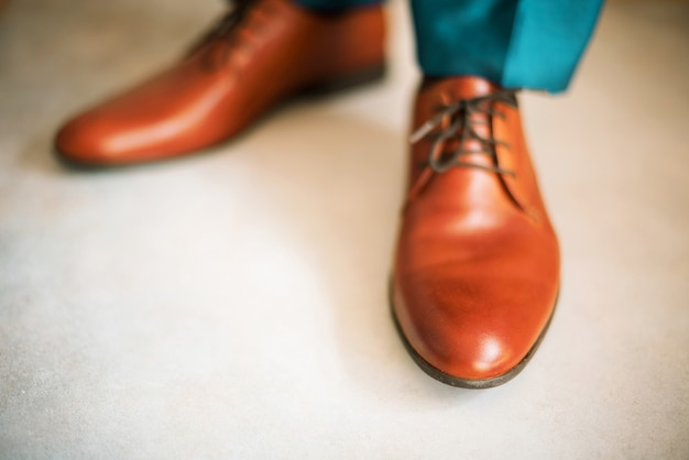Man wearing shoes on wooden floor. clothing concept, groom getting ready before ceremony. body detail of businessman.